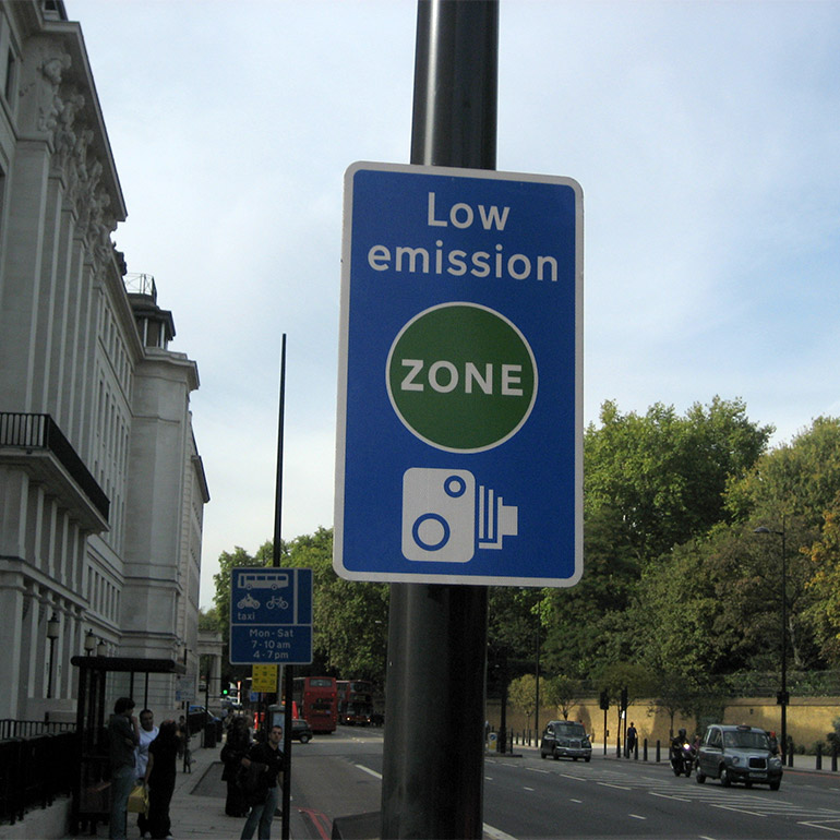 Photo of  sign indicating a Low Emission Zone, enforced by camera along a city street. Taxies, buses and pedestirans use the street.