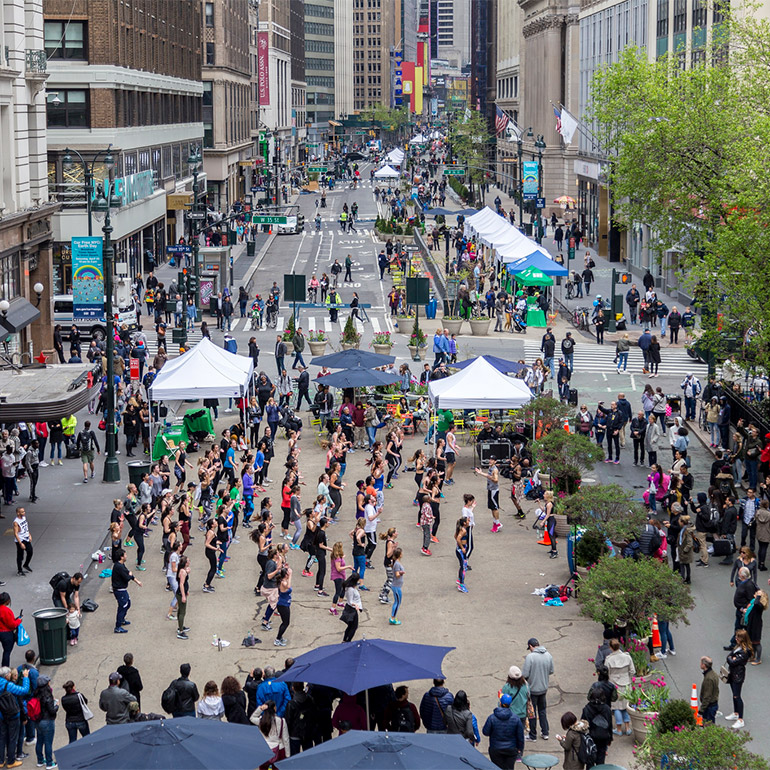 Image of a crowded pedestrian-access only street with booths, umbrellas, trees and what looks like a dance performance of two or three dozen participants taking place in the foreground. The downtown city street bends to the right in the background with more intersections, trees and popel walking throughout.