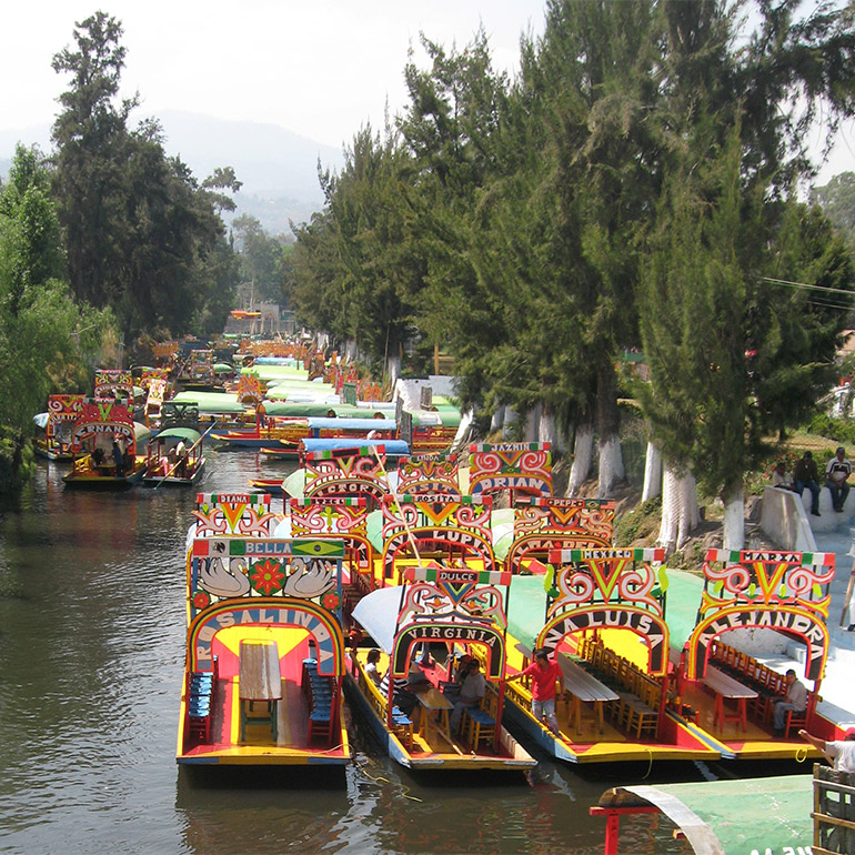 Dozens of small colorful boats with names such as Bella and Virginia travel along a river lined with large trees.