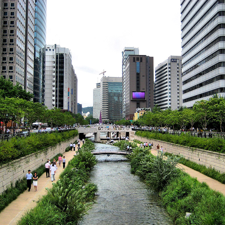 Photo showing a waterway passing through a canal with lush green foliage and pedestrian walkways on either side. Further along there are bridges of different sizes connecting the sides. In the background are half a dozen skyscrapers and what looks like an outdoor plaza with seating.