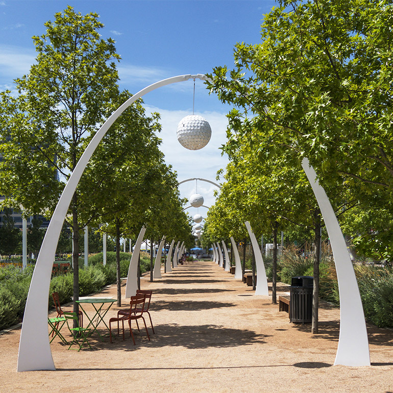 Image looking down the center of a city park path lined with trees and a tunnel-like sculpture. In the foreground is a table and set of chairs as well as a garbage can and benches in between the trees. On the arches, hang large lanterns that look like golf balls. It seems like a space that is designed for day and nighttime use.