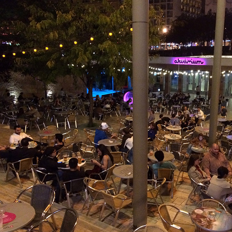 Aerial view image of an outdoor plaza with seating for nearby restaurants beneath trees and patio lights. Several dozen people sit in the space eating and drinking.