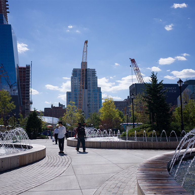 Image of an outdoor urban plaza with three water fountains and a walkway between them. Tall skyscrapers and cranes visible in the background. A few people are walking near the fountains in the center of the photo. There are trees on the outside of the plaza in the middle of the scene.