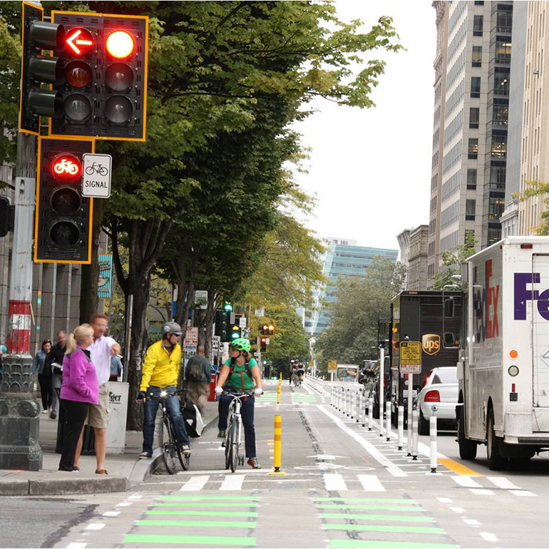 Image shows a street level view of a two way bike lane in the city, delivery trucks parked parallel to the lanes with a row of plastic bollards acting as a physical barrier. Two cyclists stopped at a red light are having a conversation and nearby them, two other pedestrians are waiting to cross the street. The street is lined by tall green trees on either side.