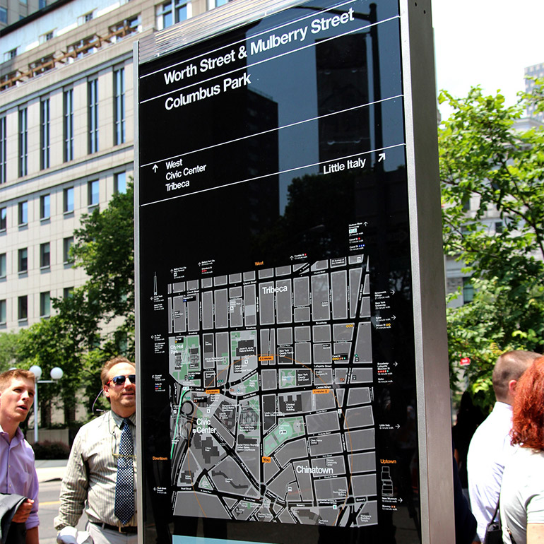 Photo of a city map posted on the street with pedestrian wayfinding details. In the background a grey office building stands behind several trees.