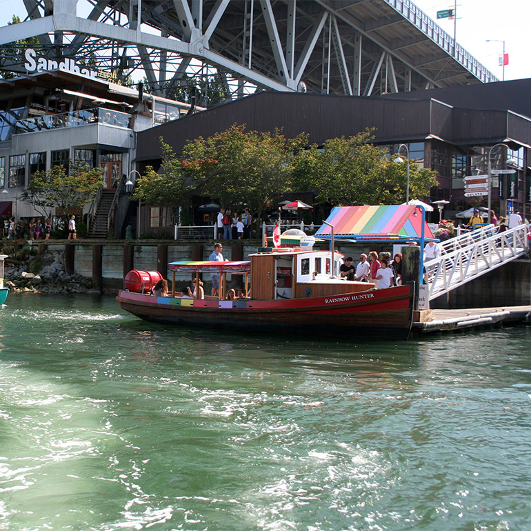 a group of people set out on a water taxi called the rainbow hunter, a wooden boat about 40 feet long with a small cabin and awning