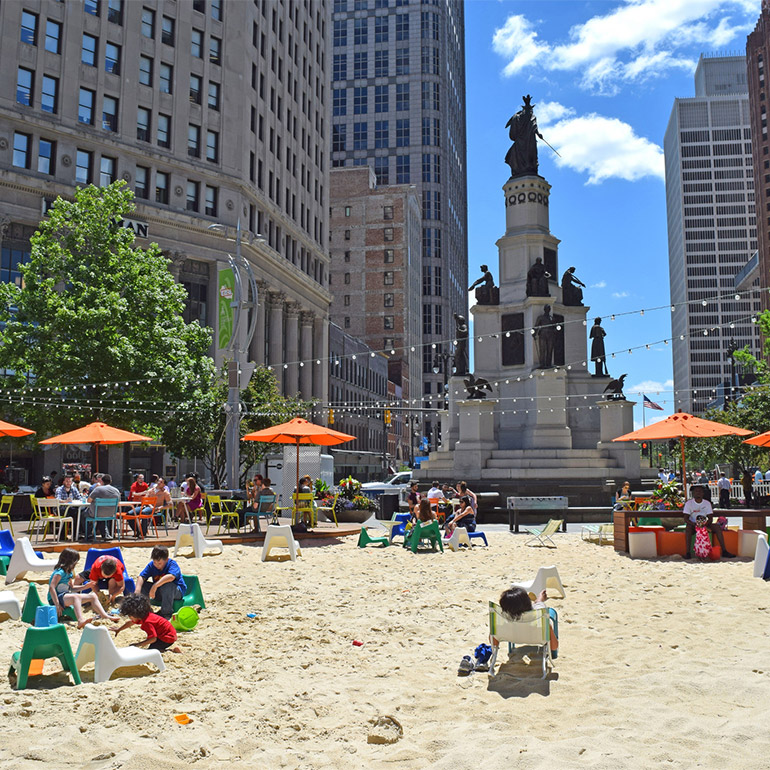 Image of a sandy park with chairs, umbrellas and tables in the middle of a city square. There is a large statue and tall, pale-colored office buildings in the background. Light green trees line the street on either side of the statue which is on the edge of the sandy park. People are seated at tables, under ubmrellas and children sit in and play with the sand.