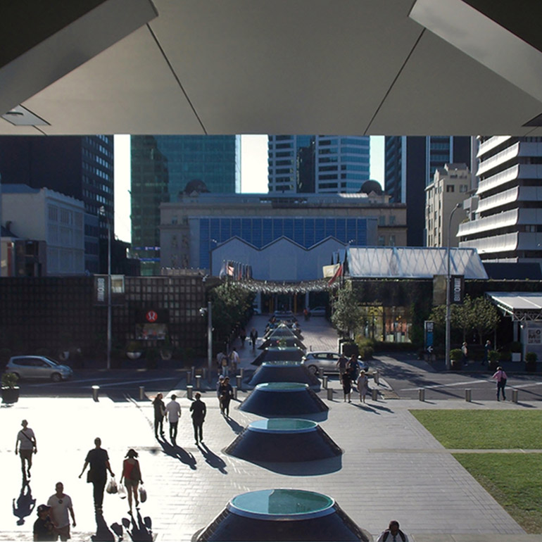 Photo of a public plaza in a downtown core with an overhang and pedestrians walking along a central walkway in the sun toward a street and larger building in the background. There is a corner of a lawn in the lower right hand corner of the photo.