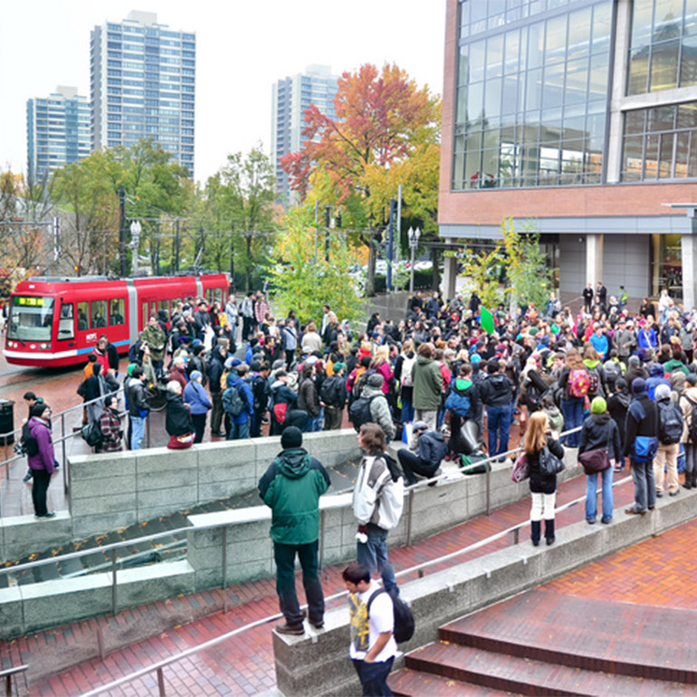 Image of a gathering of several dozen people in a downtown area plaza with a park and office buildings in the background. Between the group and the trees is a brigh red street car on its route.