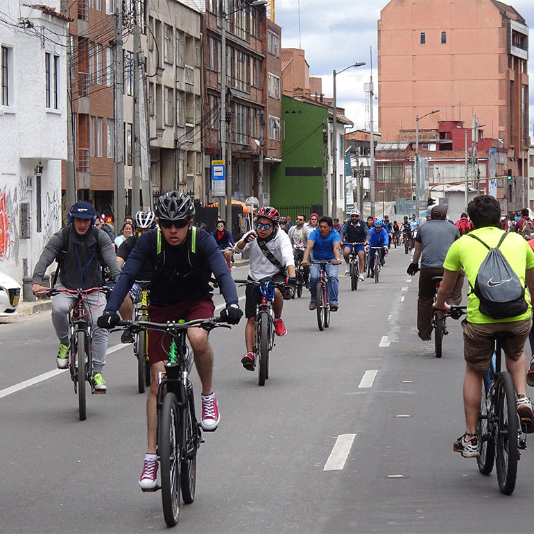 dozens of people ride bicycles down an urban street, several bicycles wide and in both directions