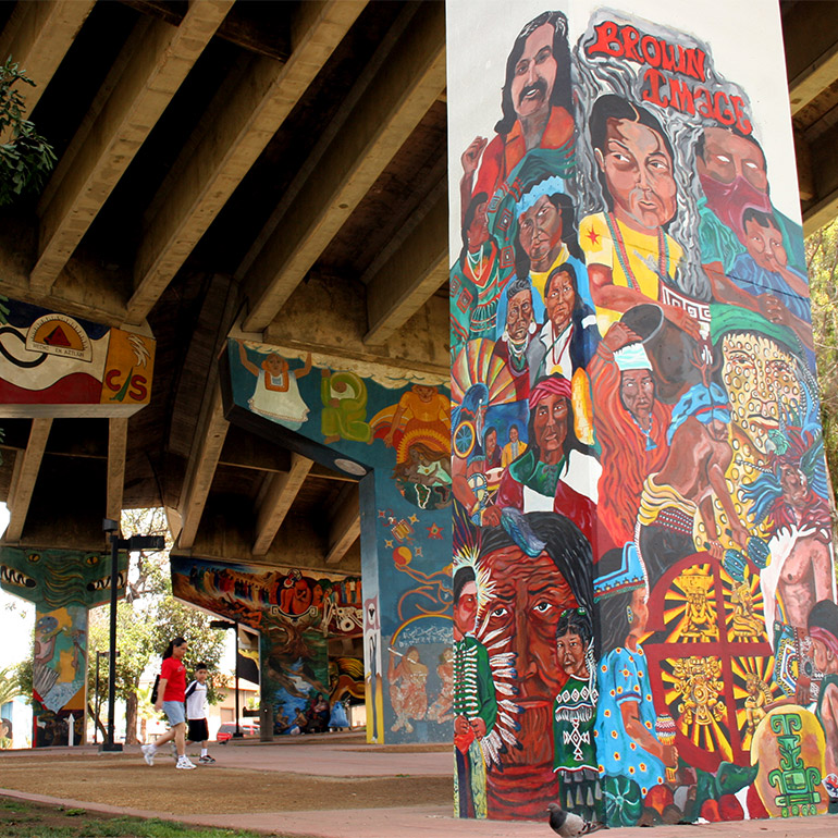 Image of children walking beneath a highway overpass, the pillars of which are covered in colorful murals depecting people of color and symbols from a diverse array of cultures.