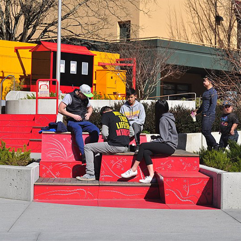 Several people sit in the sun in a park with large red stairs as part of the landscaping. It is an open-air gathering space with trees and bushes in the background.