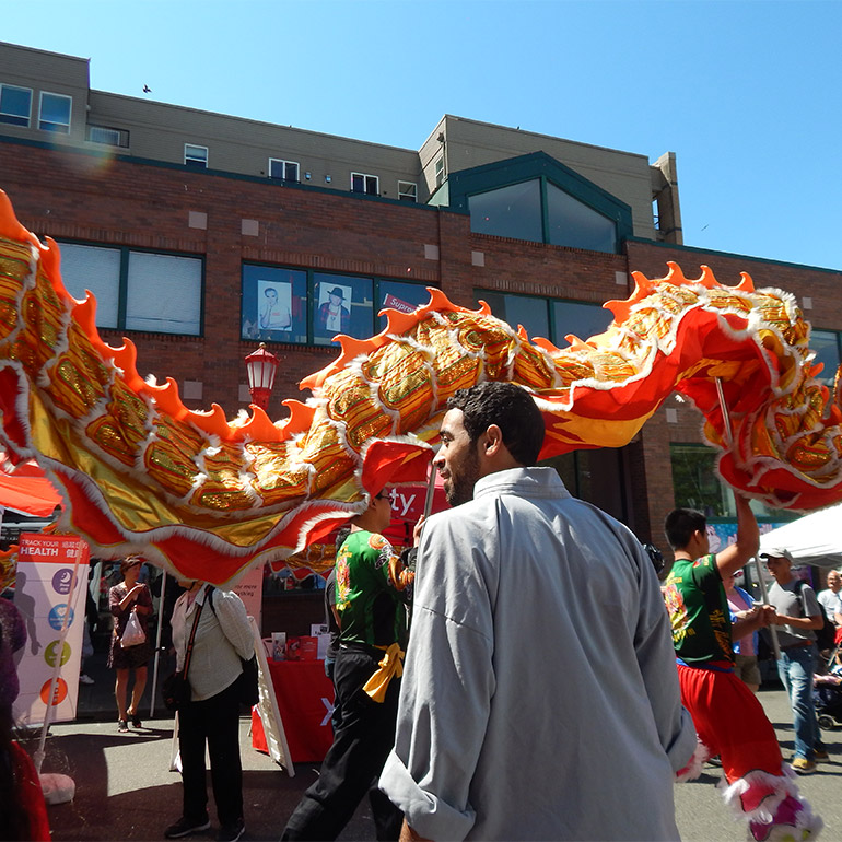 Photo shows a large cloth dragon puppet is paraded through the street at a festival in an urban setting. A person in the foreground observes the puppet's passing in front of them. There is a tall brick building in the background and blue skies above.