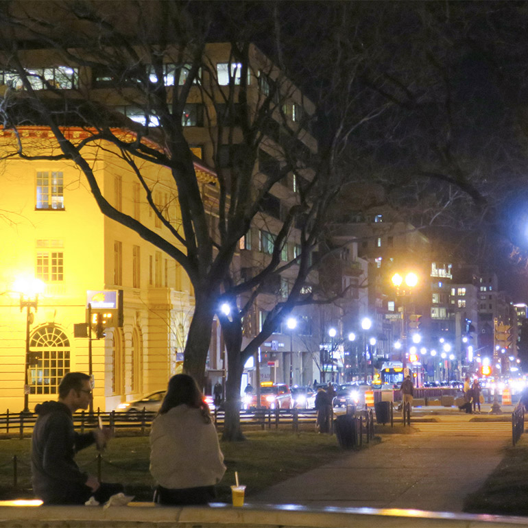 Image shows a nighttime view of a city street with street lamps on either side. A couple sits in a park beneath a large tree and face the street lamp-lined street.