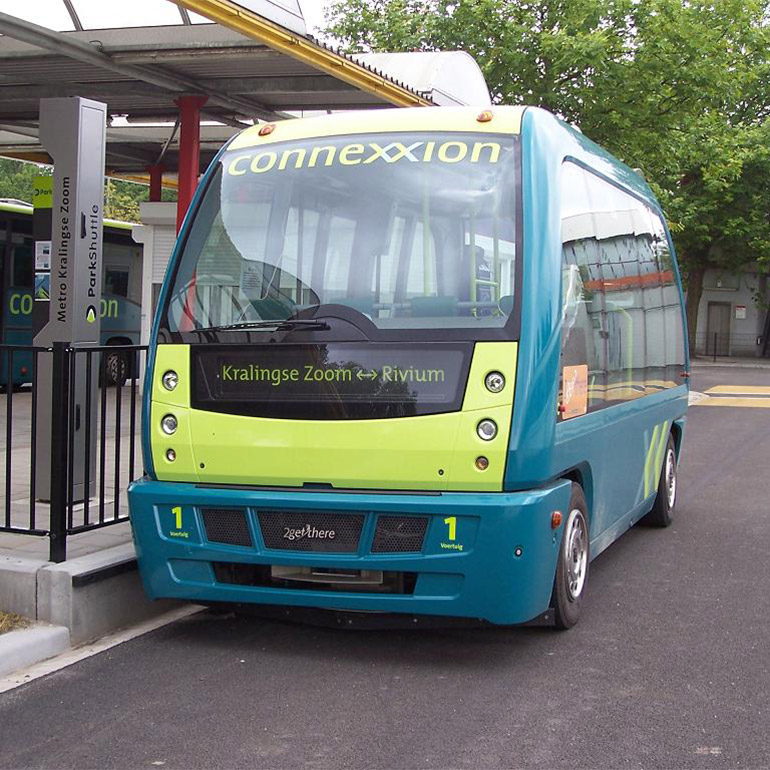 Image of a short, blue and green city bus with the word 'connection' spelled with two x's at the top of the windshield. It is parked at a bus stop and another similar looking vehicle is parked in the background.