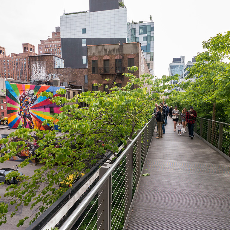 a group of people stand on the elevated highline pedestrian bridge in an urban setting surrounded by trees and with a streetart mural in the background