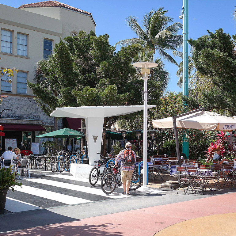 Person wearing shorts and a baseball hat walks bicycle to a bike rack in a sunny outdoor plaza with several tables and chairs with people dining outdoors on a sunny day. In the foreground, the ground is painted different colors, indicating a motorized-vehicle zone. In the background, tall trees including palm trees create shade over some of the seating area.