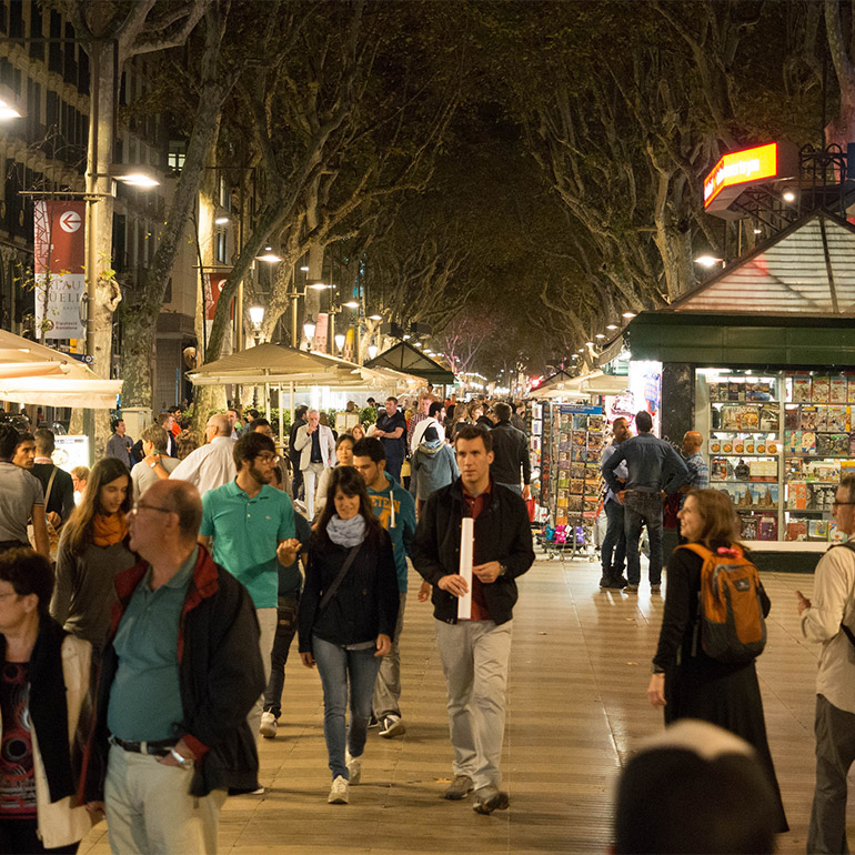 Photo of a crowded pedestrian-only street with shops, umbrellas extending into the background. Tree-lined walkway is lit up at night by streetlight and lights from the shops.