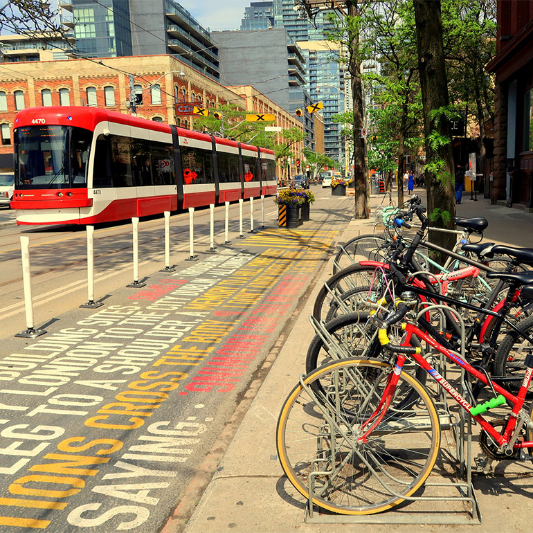 Photo shows a red and white streetcar travels down the track, along a tree-lined street and past a full rack of locked bicycles in the foreground. A bike lane is painted with different colored words, distinguishing it from the street. The lane is also protected from motor-vehicle traffic with white plastic bollards and in the background with black planter boxes.