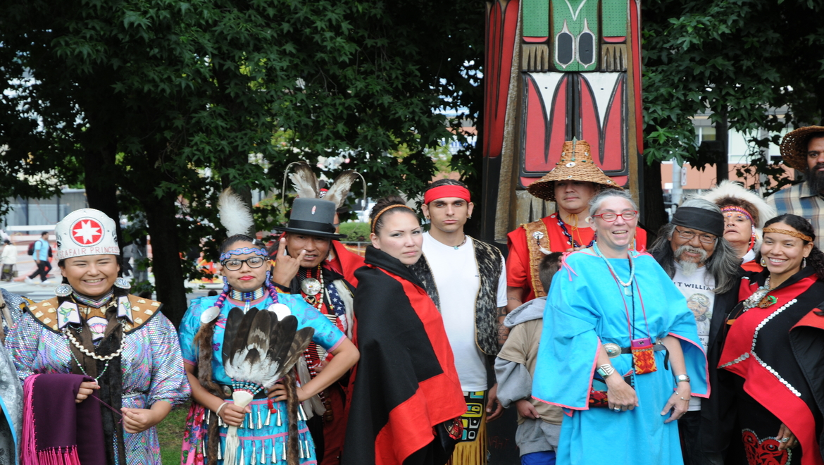 Group of people dressed in traditional native american clothing, with a Totem pole in the middle
