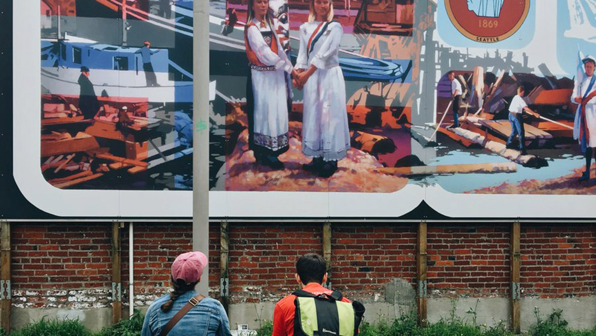 A man and a woman and a dog on leash sit on a bench looking at a Scandinavian mural in Bergen Place.