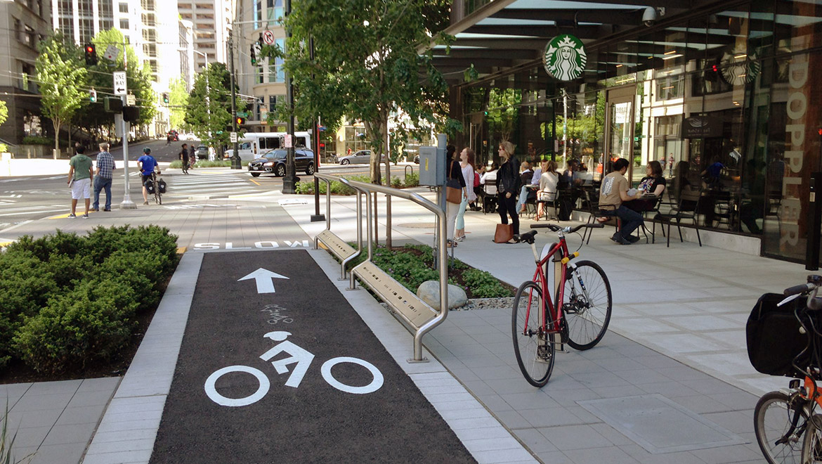 A designated bike lane extends to an intersection on a block with a Starbucks on the right side of the lane across the sidewalk. Trees create a buffer between the bike lane and sidewalk  near the entrance to Starbucks.