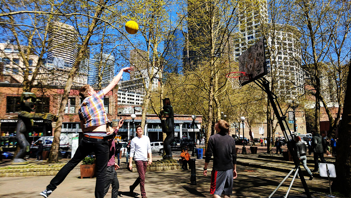 A man takes a jumpshot in a basketball game in Occidental Park. Trees and tall buildings stand in the background behind the people playing basketball.