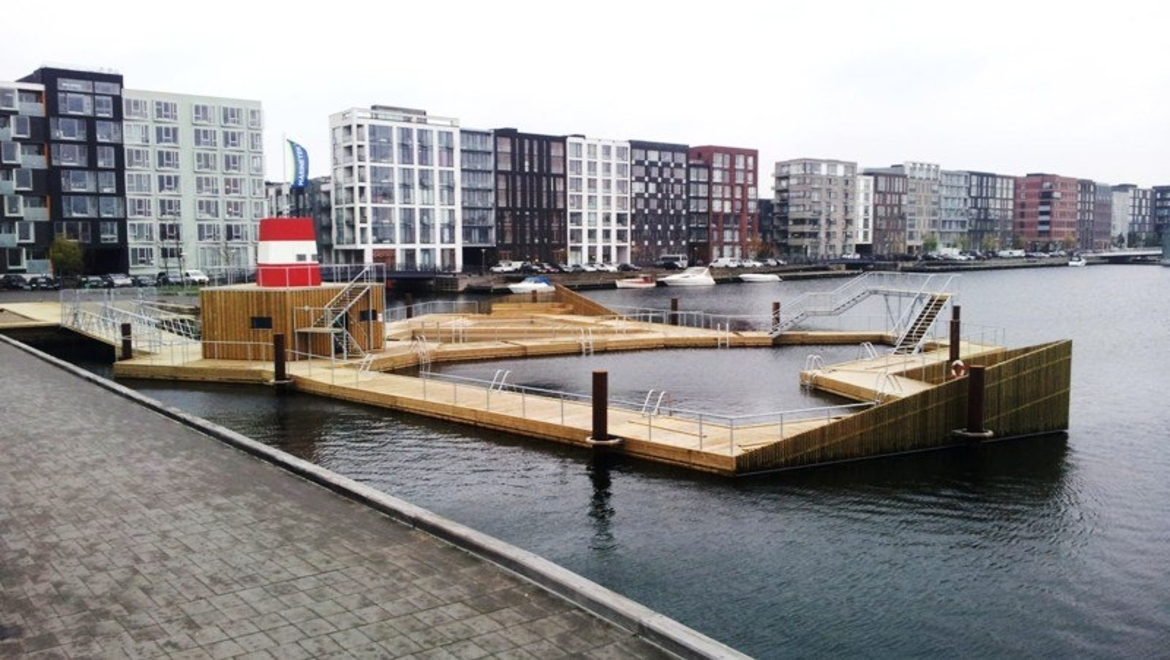 A dock beside a row of 15 or so apartment buildings along the water front is designed in the shape of a swimming pool, with different deck heights and multiple ladders to get in and out of the water. There is a concrete walkway in the foreground which looks like it extends further into the water than the pool-like dock adjacent to it.