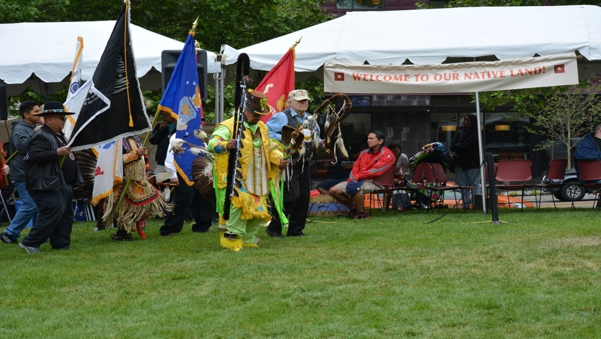 Native American celebration with traditional dress, flags and dancing